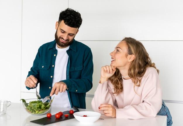 Adorable couple cuisinant ensemble à la maison