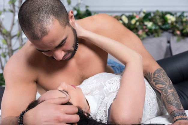 Adorable couple international d'homme à la poitrine nue, les mains tatouées et la femme brune se regardent en position couchée sur le lit douillet gris dans la chambre