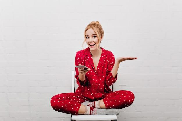 Adorable dame excitée aux cheveux blonds assis sur un mur blanc. jolie fille en costume de nuit rouge tenant la cellule et exprimant des émotions positives.
