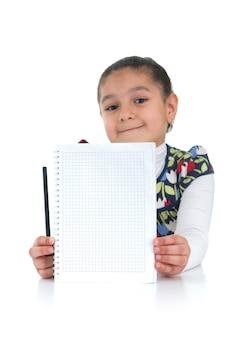 Adorable écolière avec des devoirs faits sur fond blanc