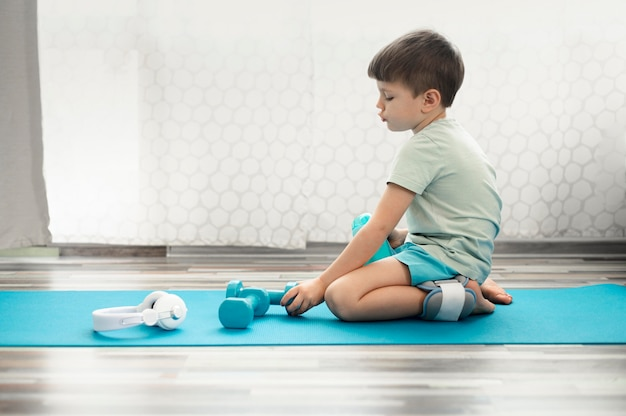 Adorable enfant assis sur un tapis de yoga