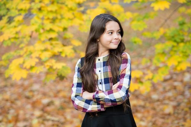 Adorable enfant aux cheveux longs, profitez de la nature automnale, de la saison.