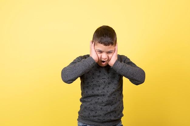 Adorable enfant dans des vêtements décontractés debout et couvrant ses oreilles.