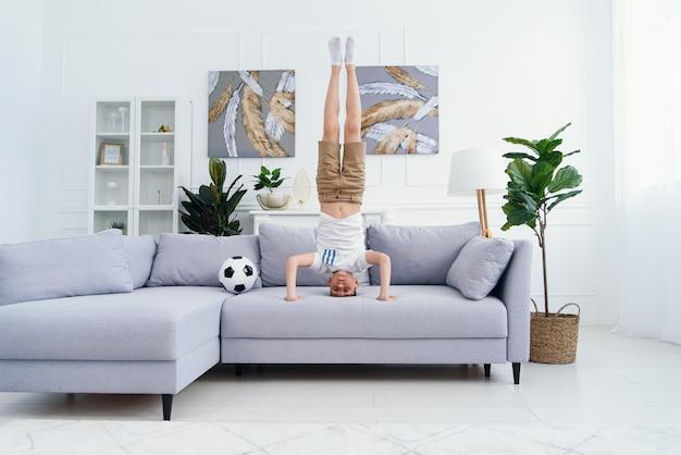 Adorable enfant debout sur la tête sur le canapé à la maison