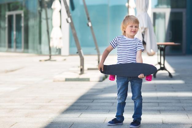 Adorable enfant à l'extérieur. joli enfant assez gai tenant la planche à roulettes garçon occasionnel sur l'heure d'été patinage sur une planche à roulettes.