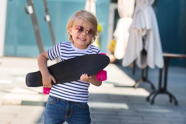 Adorable enfant à l'extérieur. joli joli enfant à lunettes de soleil souriant à la caméra. garçon décontracté sur l'heure d'été patiner sur une planche à roulettes.