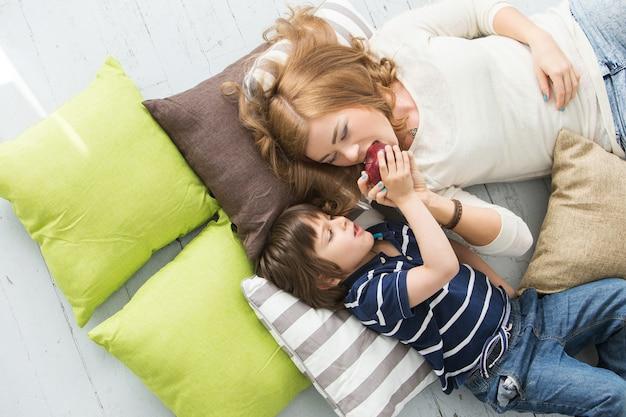 Adorable enfant avec mère mange une pomme