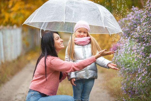 Adorable enfant avec sa jeune mère s'amusant à l'automne sous l'égide. joyeuse famille à l'automne