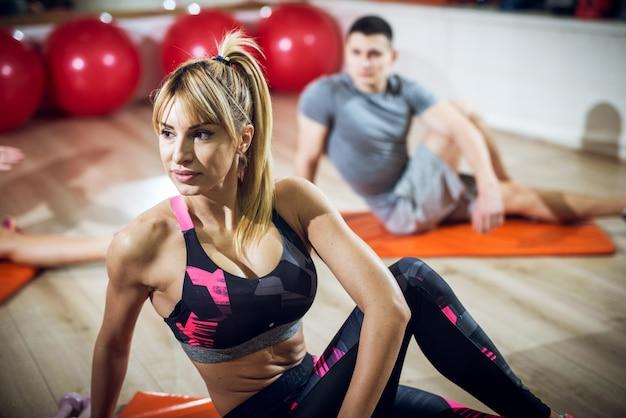 Adorable entraîneur de fitness actif de forme blonde sexy ayant des cours d'entraînement dans la salle de gym tout en étant assis sur le sol et en regardant loin.