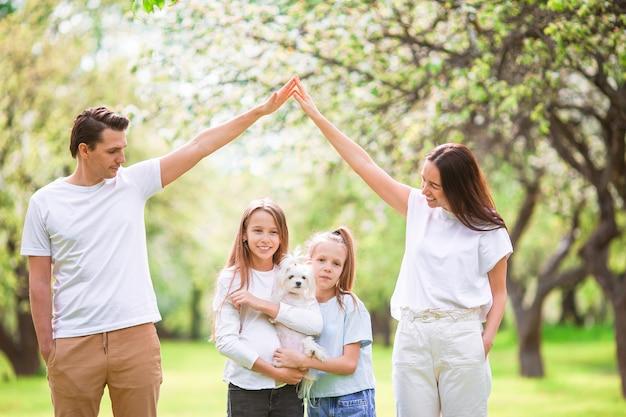 Adorable famille dans un jardin de cerisier en fleurs par une belle journée de printemps
