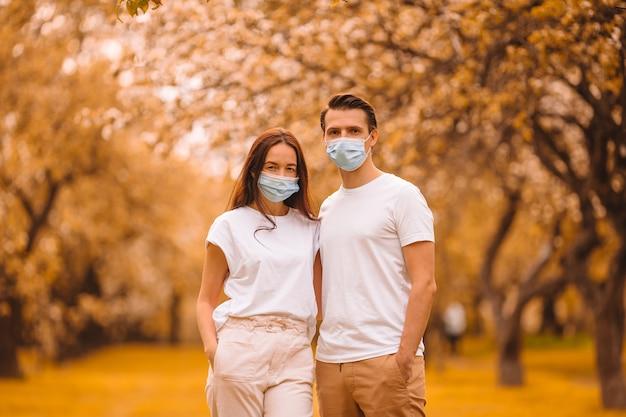 Adorable famille dans un jardin de cerisiers en fleurs dans des masques