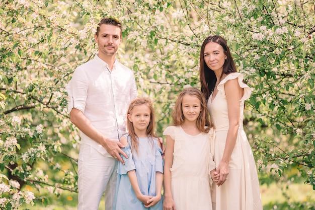 Adorable famille dans un jardin de fleurs de cerisier sur une belle journée de printemps