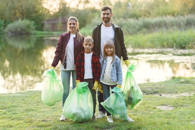 Une adorable famille de parents et d'enfants tient des sacs poubelles en plastique après le nettoyage du territoire environnant près du lac