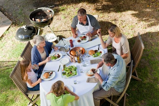 Adorable famille en train de manger dans le jardin