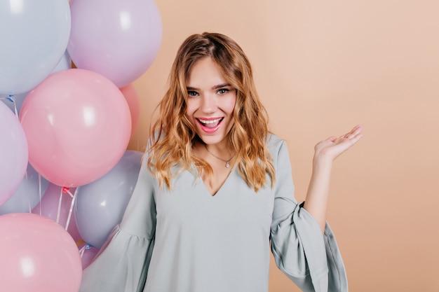 Adorable femme d'anniversaire avec maquillage tendance posant sur un mur léger