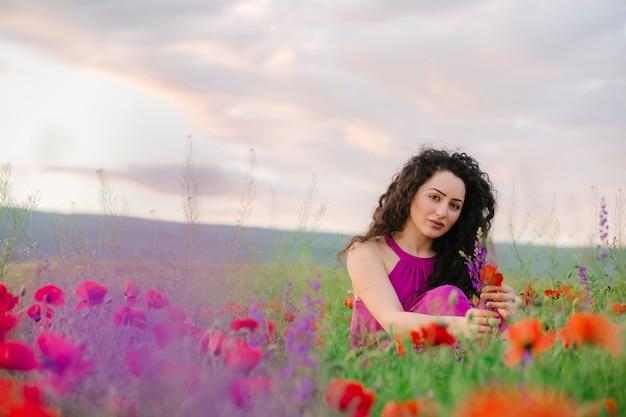 Adorable femme assise et appréciant la fleur de fleurs sauvages dans le pré