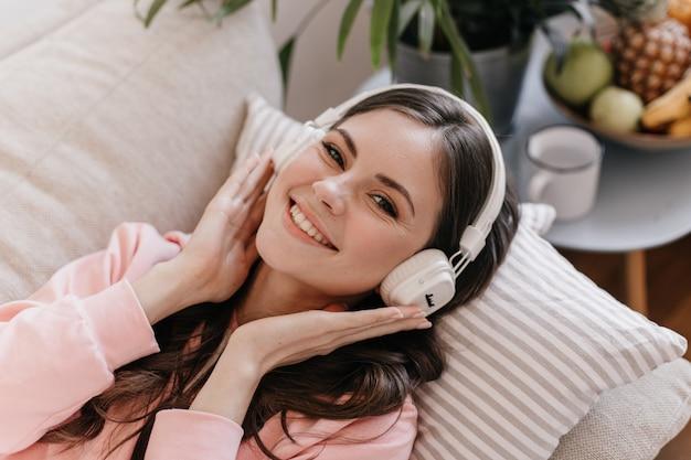 Adorable femme aux cheveux noirs écoute de la musique sur des écouteurs, sourit doucement et s'allonge sur un canapé
