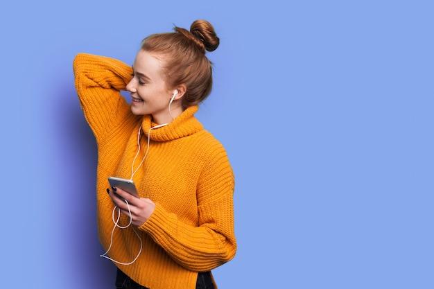 Adorable femme aux cheveux rouges et taches de rousseur écoute de la musique sur un mur de studio bleu avec espace libre