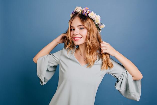 Adorable femme blanche en guirlande de fleurs dansant sur mur bleu