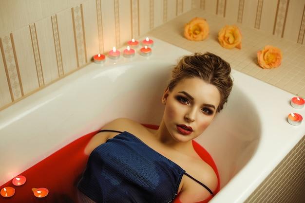 Adorable femme blonde au maquillage professionnel prend un bain avec de l'eau rouge et des bougies