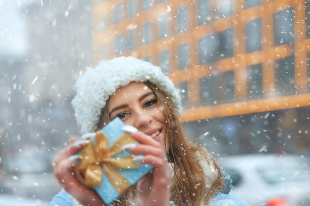 Adorable femme blonde porte une casquette tricotée blanche tenant une boîte cadeau bleue, marchant dans la ville pendant les chutes de neige