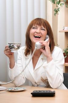 Adorable femme brune blanche caucasienne souriante parlant au téléphone au bureau pendant la pause. fille tenant une tasse de café. cuillère à thé sur plat, calculatrice sur table.