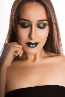 Adorable femme brune avec une peau parfaite et un maquillage vert métallique créatif. closeup portrait au studio sur fond blanc