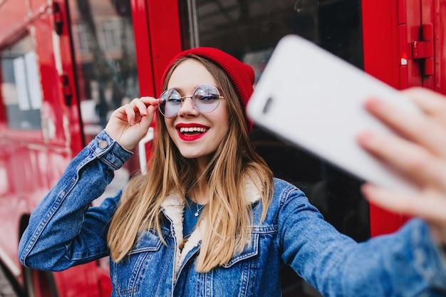 Adorable femme caucasienne touchant ses lunettes de manière ludique tout en faisant selfie près du bus.