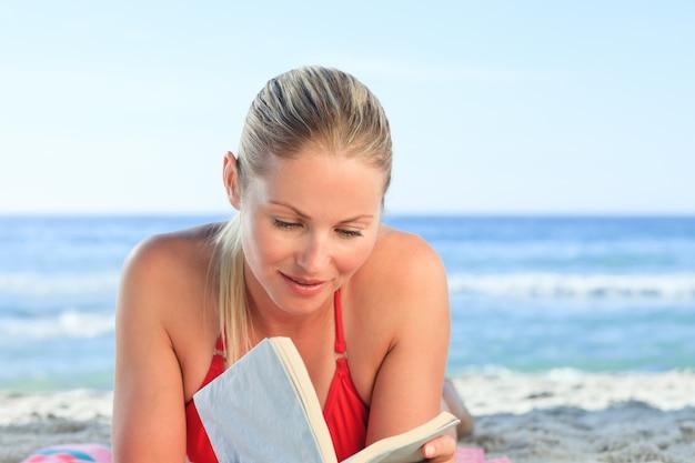 Adorable femme lisant un livre sur la plage