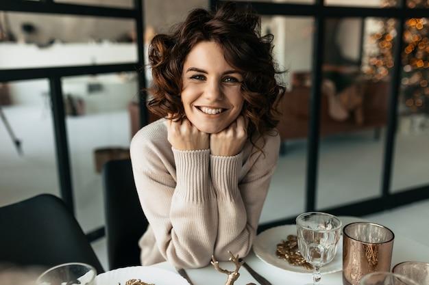 Adorable femme moderne élégante avec des cheveux ondulés posant en attendant le soir de noël