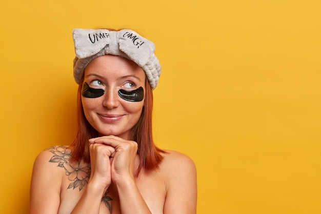 Adorable femme réfléchie aux cheveux roux, se tient nue à l'intérieur, bénéficie de soins de beauté, porte des patchs de collagène de récupération d'hydrogel pour éliminer les cernes et les poches sous les yeux, rajeunit la peau.
