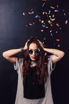 Adorable femme s'amusant avec des confettis