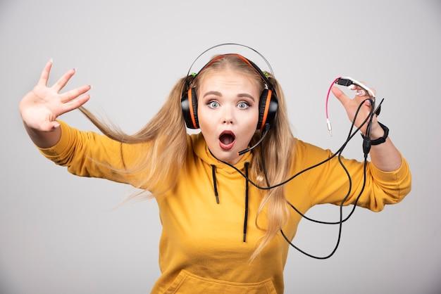 Adorable femme en sweat à capuche jaune écoutant de la musique dans les écouteurs.