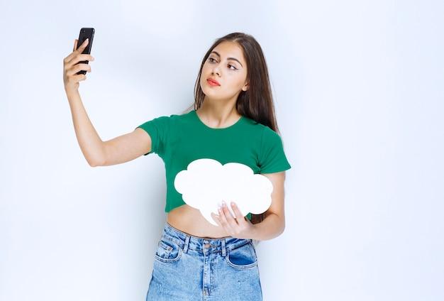 Adorable femme tenant une bannière de bulle de dialogue et prenant un selfie.
