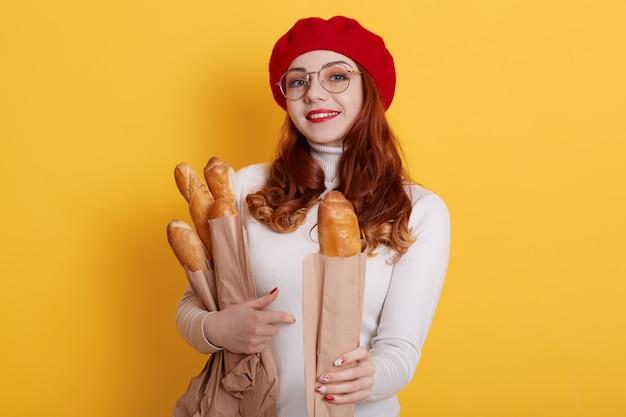 Adorable femme tenant un sac en papier avec de longues baguettes de pain, en offre une à quelqu'un, portant une chemise blanche, un béret rouge et des lunettes sur jaune