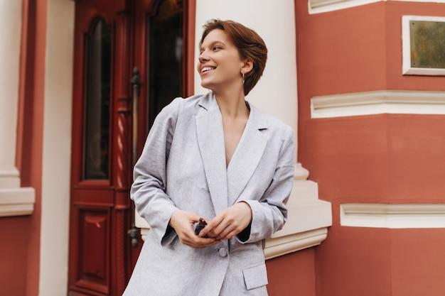 Adorable femme en veste grise souriant et posant à l'extérieur. dame aux cheveux courts en costume élégant en riant et s'appuyant sur le mur