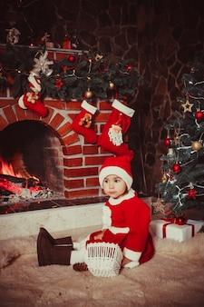 Adorable fille assise près de la cheminée et jouer avec des cônes - décorations de noël