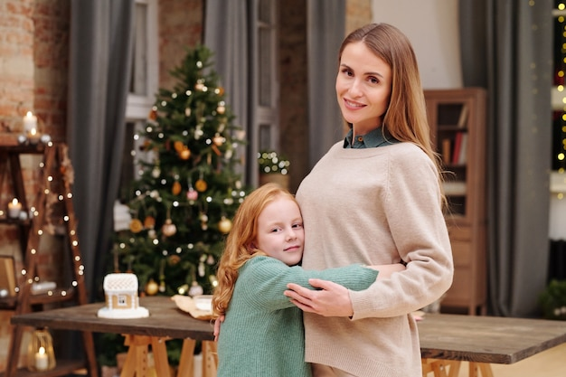 Adorable fille aux longs cheveux roux embrassant sa mère tout en vous regardant contre sapin décoré et bougies allumées à la maison