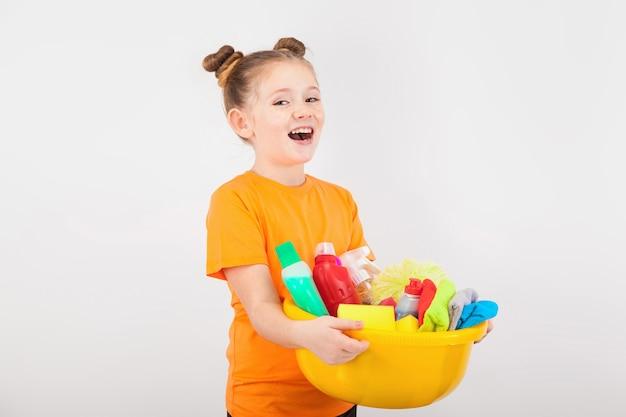 Adorable fille avec une bassine pleine de produits de nettoyage