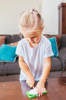 Adorable fille blonde coupe de la pâte à modeler