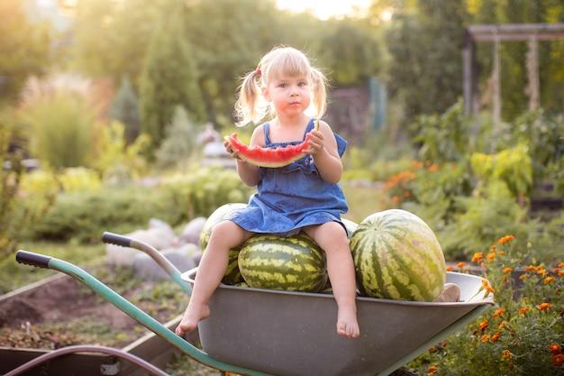 Adorable fille blonde mange une tranche de melon d'eau à l'extérieur