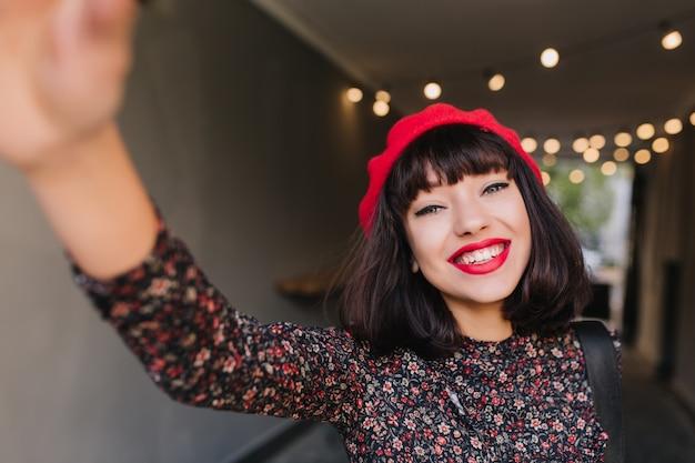 Adorable fille brune française avec un maquillage élégant et une coiffure courte s'amusant avec un appareil photo sur fond flou. jolie jeune femme aux cheveux noirs en vêtements vintage faisant selfie et souriant joyeusement