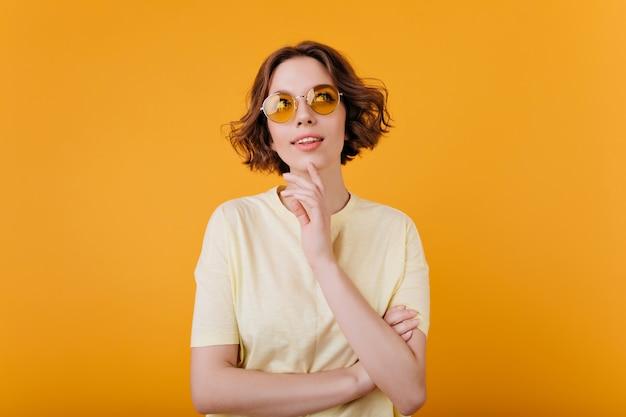 Adorable fille caucasienne avec une expression de visage pensif touchant son menton. belle jeune femme aux cheveux ondulés bruns isolés sur un mur lumineux.