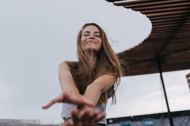 Adorable fille caucasienne exprimant des émotions positives. charmante femme blonde s'amusant tout en posant.