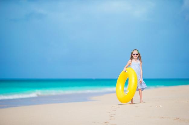 Adorable fille avec cercle de caoutchouc gonflable sur une plage blanche prête pour la natation