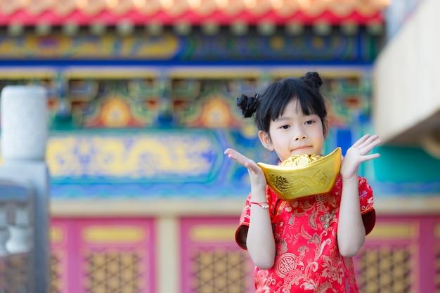 Adorable fille chinoise heureuse recevant un lingot d'or le nouvel an chinois