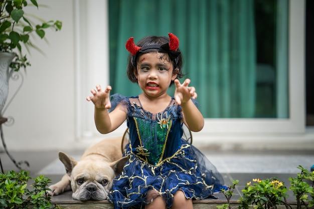 Adorable fille en costume d'halloween assise en plein air avec son chien