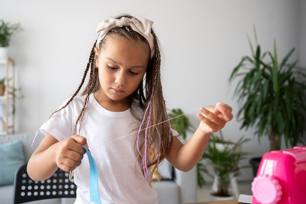 Adorable fille cousant des vêtements à la main