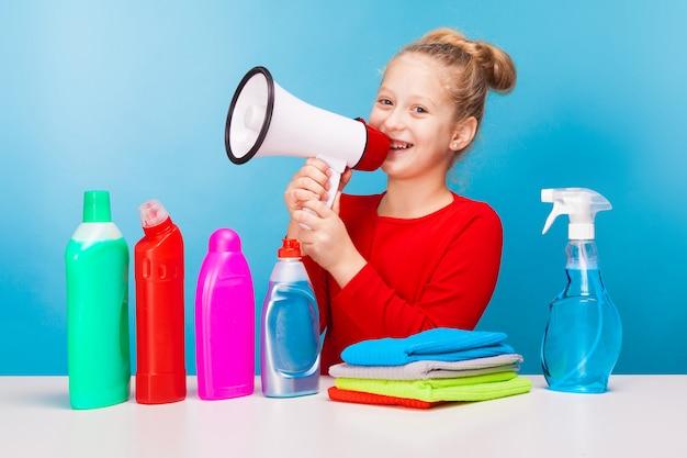 Adorable fille avec divers nettoyeurs tenant un haut-parleur
