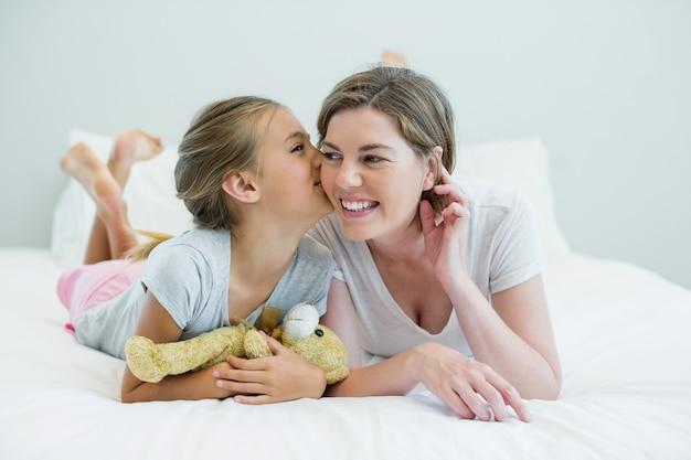 Adorable fille embrassant sa mère allongée sur un lit